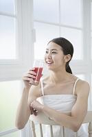 野菜ジュースを飲みながら微笑む20代日本人女性