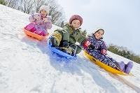 雪の公園でソリ遊びをする日本人の子供