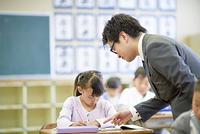 小学校の先生と授業を受ける子供