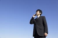 青空の下で電話をする若いビジネスマン