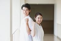廊下でポーズをとる笑顔の若い看護師