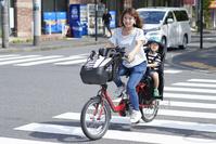 子供を自転車に乗せる母親