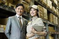 倉庫にいる作業員とビジネスマン