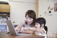 ノートパソコンを見る女の子と母親