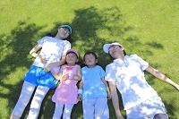 スポーツウェアを着て芝生で寝転ぶ家族