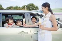 ソフトクリームを車中の家族に手渡す女性