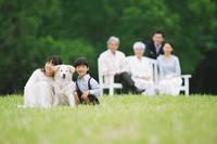 芝生でくつろぐ三世代家族