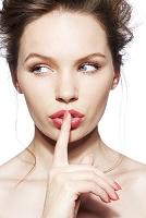 唇に指を当てる外国人女性