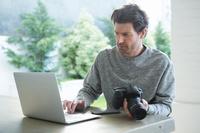 デジタルカメラとパソコンを利用する外国人男性
