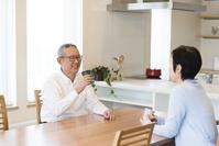 向かい合って会話をしている老夫婦