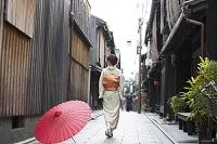 祇園の通りに立つ着物の女性