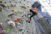 クライミングウォールを登る外国人女性