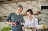 ワインを注ぐシニアの日本人男性