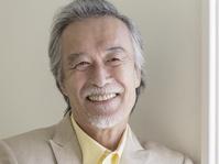 壁にもたれた笑顔のシニアの日本人男性
