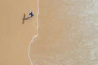 ビーチを歩くサーファー