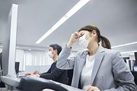 目頭を押さえる日本人ビジネスウーマン