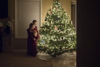 クリスマスツリーの飾りつけをする子供達