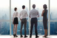 窓辺から遠くを見るビジネスチーム