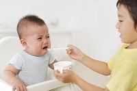 赤ちゃんに離乳食を食べさせるお兄ちゃん