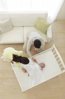 ベビーベッドで眠る新生児を見守るパパとママ