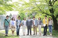教授を囲み微笑む8人の男女大学生