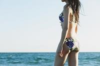 海を眺める水着の女性