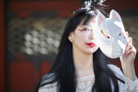 狐面を持った狐メイクの日本人女性