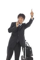 携帯電話をかけながら手をあげる日本人ビジネスマン