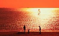 光る海と浜辺の親子のシルエット