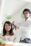美容師に髪を切ってもらう20代女性