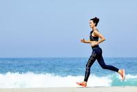 夏の海辺をジョギングをする女性