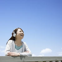 ヘッドホンで音楽を聴く日本人女性