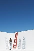 壁にかかった梯子と空を見つめる女性