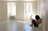 部屋の壁にもたれる孤独な少女