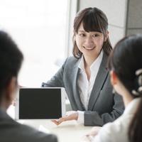 タブレットを持ち説明をする日本人ビジネスウーマン