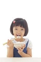 お茶碗のご飯を食べるおかっぱの女の子