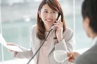 電話しながら応対する日本人ビジネスウーマン