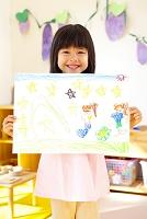 絵を持って微笑む幼稚園女児