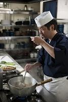煮魚の味見をする調理師