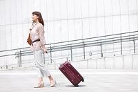 スーツケースを引いて歩く中高年日本人女性
