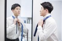 鏡に向かいネクタイを結ぶビジネスマン