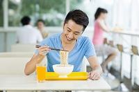 カフェでヌードルを食べる男性