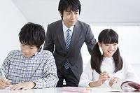 勉強する小学生と指導する教師