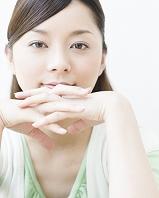 手を組んで微笑む日本人女性