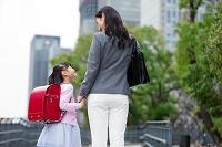 手を繋いで歩く女の子と母親の後姿