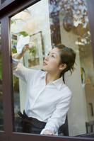 窓拭きをするエプロン姿の日本人女性