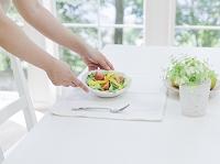 サラダをテーブルに置く手