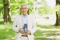 新緑とカメラを持つシニアの日本人男性