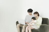 ソファでパソコンをしている日本人家族
