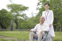 車椅子に乗るシニア日本人男女介護士